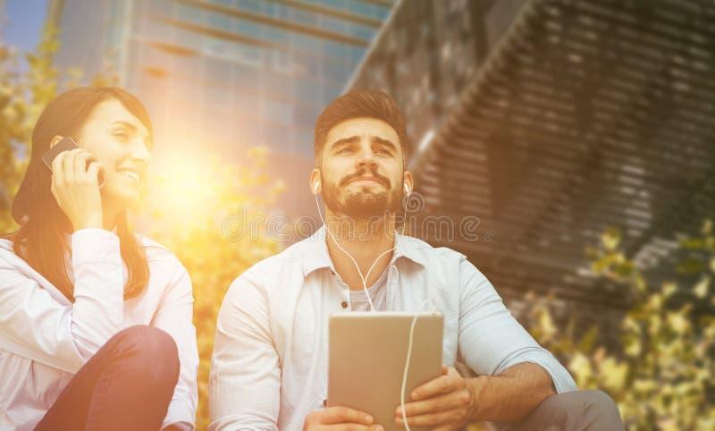 Złożony wizerunek mężczyzna słuchająca muzyka z hełmofonem podczas gdy kobieta używa jej telefon komórkowego obraz stock