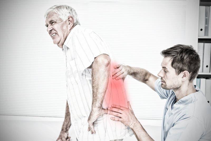 Złożony wizerunek męski physiotherapist egzamininować starszy obsługuje z powrotem zdjęcia royalty free