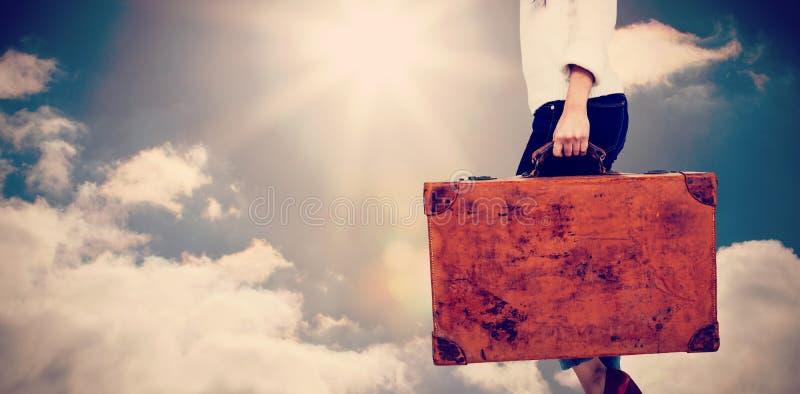 Złożony wizerunek niska sekcja kobiety przewożenia rocznika walizka zdjęcie royalty free