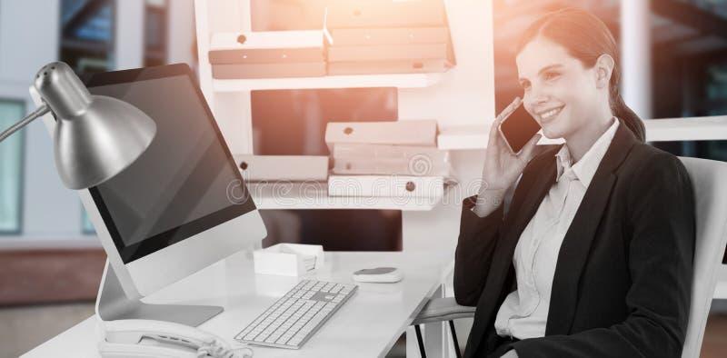Złożony wizerunek opowiada na telefonie komórkowym przy biurkiem z komputerem uśmiechnięty bizneswoman obrazy stock