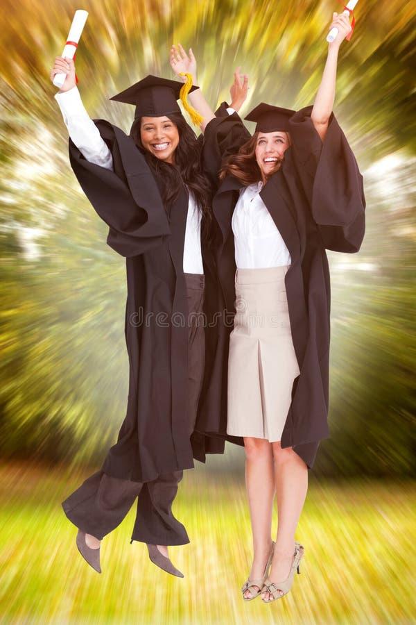 Złożony wizerunek pełna długość dwa kobiety świętuje w powietrzu zdjęcia royalty free