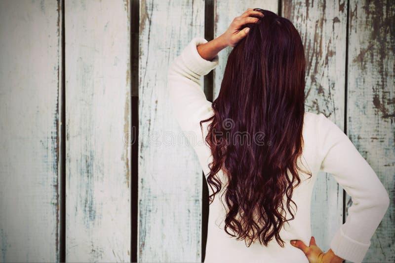 Złożony wizerunek pełnej długości tylni widok brunetka z ręką w włosy obraz royalty free