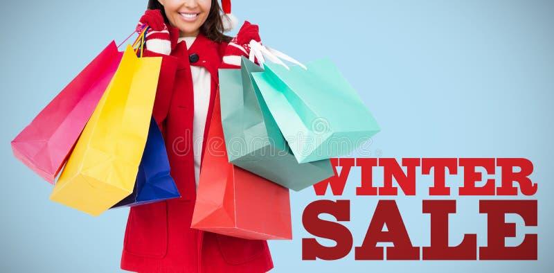 Złożony wizerunek piękna brunetka z Santa mienia kapeluszowymi torba na zakupy obrazy royalty free