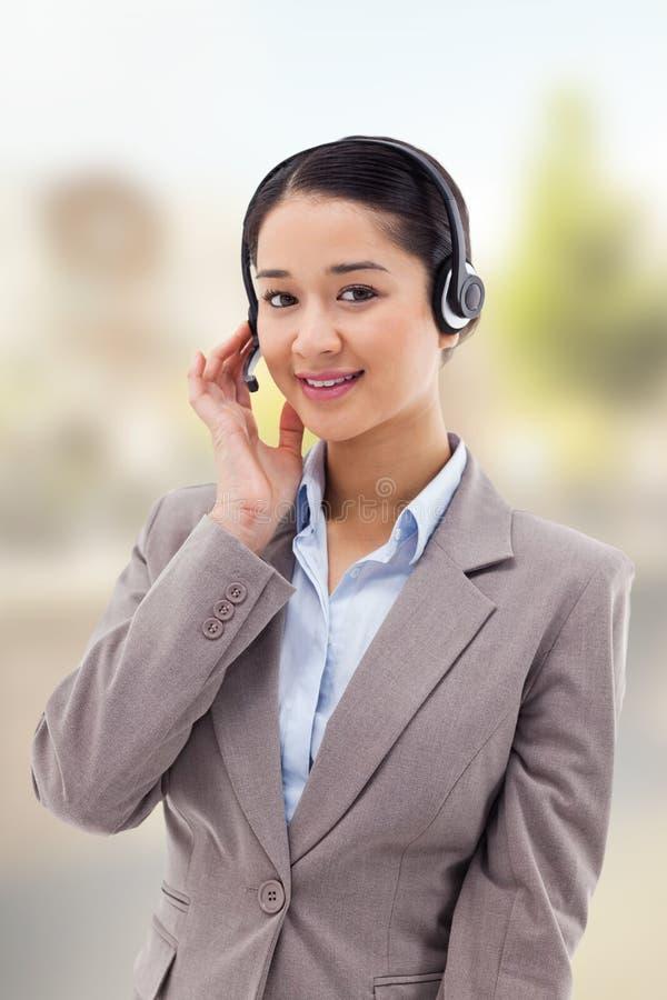 Złożony wizerunek portret dobry przyglądający operator pozuje z słuchawki zdjęcie stock