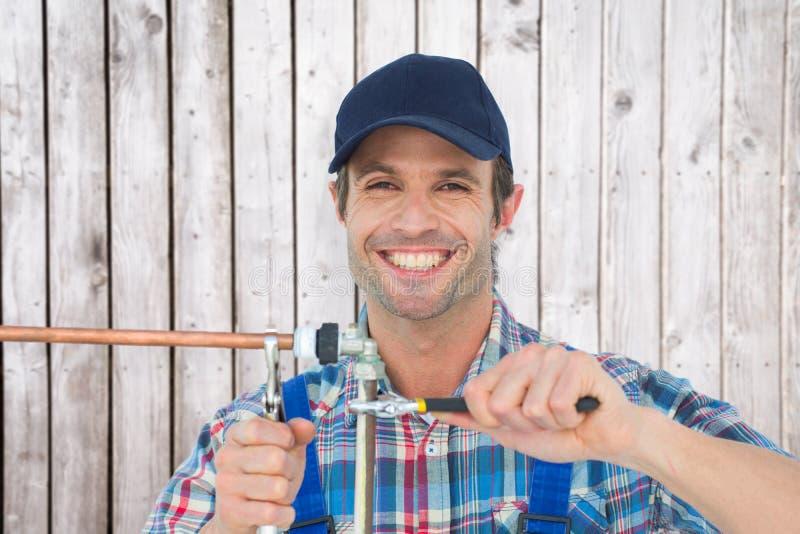 Złożony wizerunek portret szczęśliwa hydraulika naprawiania drymba fotografia stock