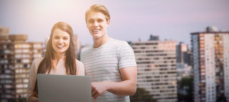 Złożony wizerunek pozuje z laptopem młody ono uśmiecha się obrazy stock