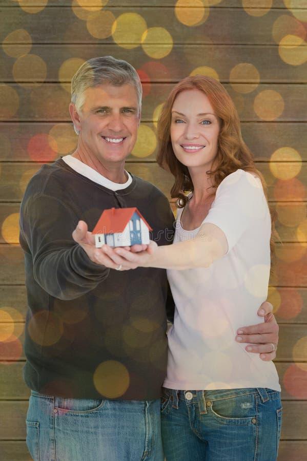 Złożony wizerunek przypadkowy pary mienia mały dom obrazy royalty free