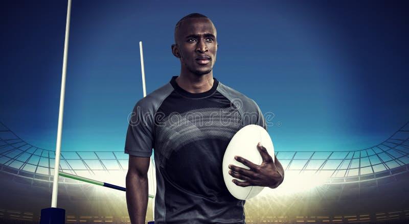Złożony wizerunek rozważna atlety mienia rugby piłka obrazy royalty free