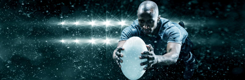 Złożony wizerunek rugby gracza doskakiwanie podczas gdy łapiący piłkę zdjęcie stock