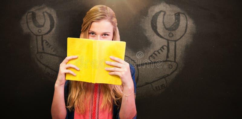 Złożony wizerunek studencka nakrycie twarz z książką w bibliotece zdjęcie stock