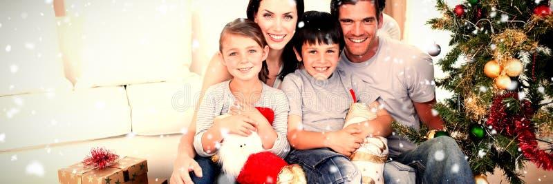 Złożony wizerunek szczęśliwa rodzina przy bożymi narodzeniami synchronizuje trzymać udziały teraźniejszość fotografia stock