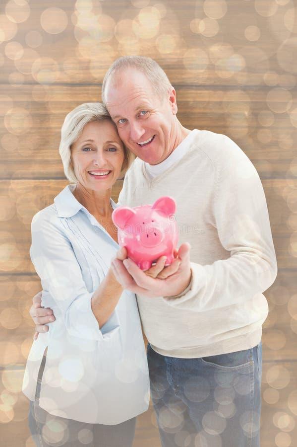 Złożony wizerunek szczęśliwy dorośleć pary ono uśmiecha się przy kamerą pokazuje prosiątko banka zdjęcie royalty free