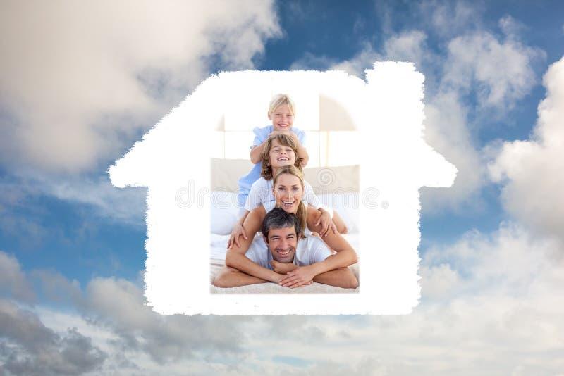 Złożony wizerunek szczęśliwy rodzinny mieć zabawę na łóżku fotografia stock