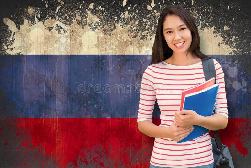 Złożony wizerunek szkoły wyższa dziewczyny mienie rezerwuje z zamazanymi uczniami w parku obrazy royalty free