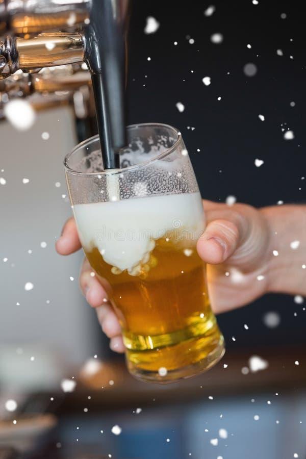 Złożony wizerunek trzyma szklanego podsadzkowego piwo ręka zdjęcie royalty free