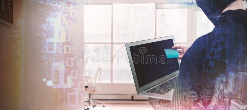 Złożony wizerunek tylni widok hacker używa laptop i kredytową kartę fotografia royalty free