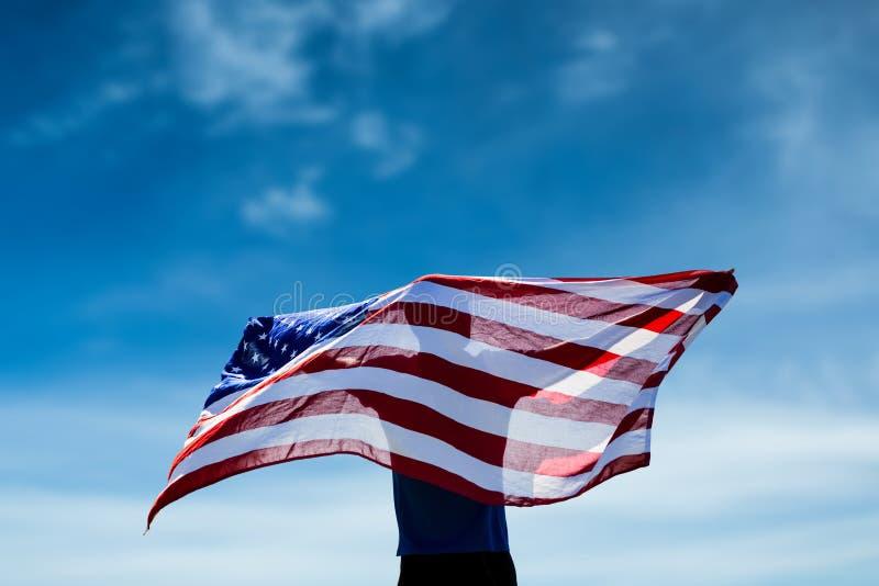 Złożony wizerunek tylni widok pozuje z flaga amerykańską sportowiec fotografia stock