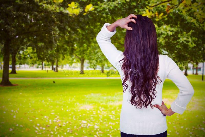 Złożony wizerunek tylni widok zmieszana kobieta z ręką w włosy obraz stock
