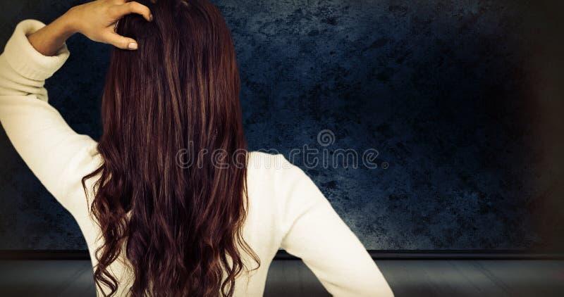 Złożony wizerunek tylni widok zmieszana kobieta z ręką w włosy zdjęcia stock