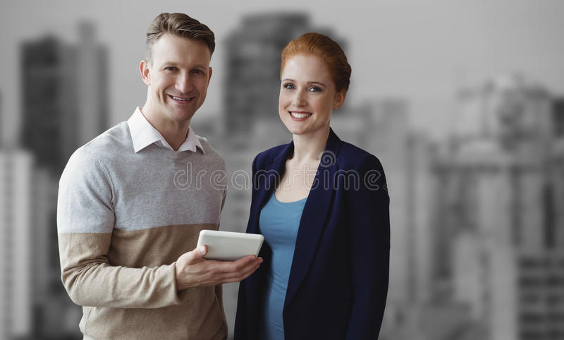 Złożony wizerunek uśmiechnięci ludzie biznesu używa cyfrową pastylkę fotografia stock