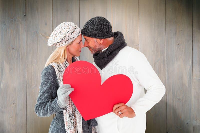 Złożony wizerunek uśmiechnięta para w zimy modzie pozuje z kierowym kształtem fotografia royalty free
