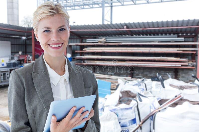 Złożony wizerunek uśmiechnięty buisnesswoman używać cyfrową pastylkę obrazy royalty free