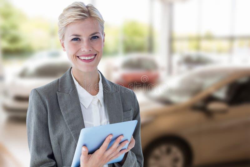 Złożony wizerunek uśmiechnięty buisnesswoman używać cyfrową pastylkę fotografia royalty free