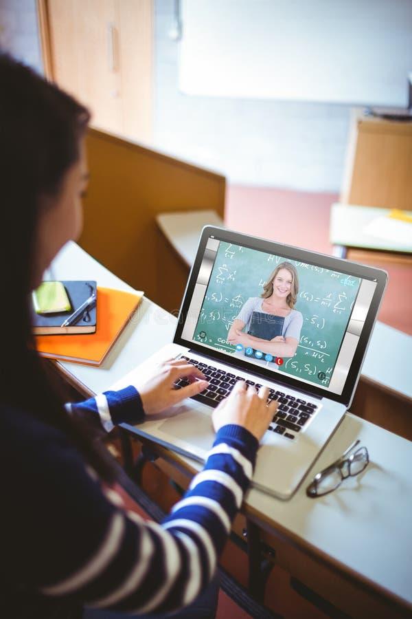 Złożony wizerunek uśmiechnięty nauczyciela mienia notatnik przed blackboard obraz stock