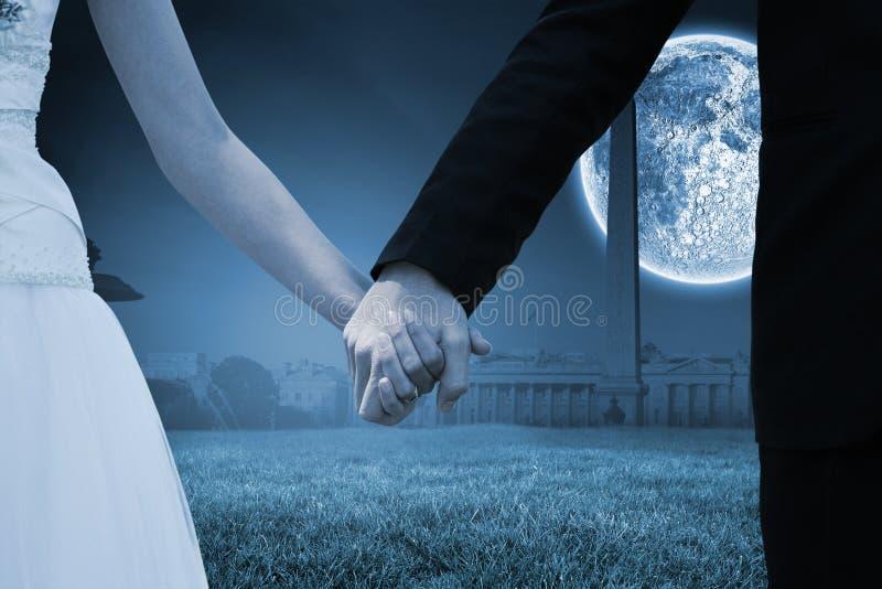 Złożony wizerunek w połowie sekcja nowożeńcy pary mienia ręki w parku obraz royalty free