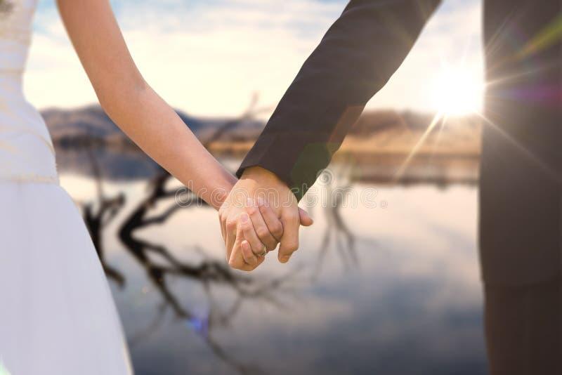 Złożony wizerunek w połowie sekcja nowożeńcy pary mienia ręki w parku zdjęcia royalty free