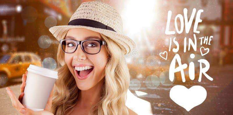 Złożony wizerunek wspaniały uśmiechnięty blondynka modniś przedstawia oddaloną filiżankę zdjęcie stock