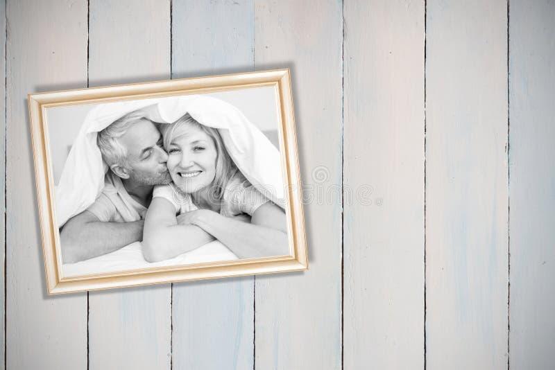 Złożony wizerunek zbliżenie dojrzały mężczyzna całowania kobiety policzek w łóżku fotografia royalty free