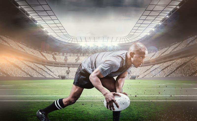Złożony wizerunek zdecydowany atlety chylenie podczas gdy bawić się rugby zdjęcia stock