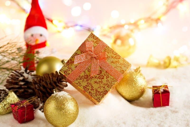 Złociści Bożenarodzeniowi prezentów pudełka z bałwanem i bauble na śniegu w zaświecać kolorowy fotografia stock