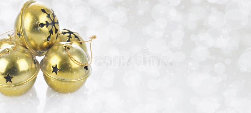 Złociści dźwięczenie dzwony na śnieżnym bokeh osrebrzają tło fotografia stock