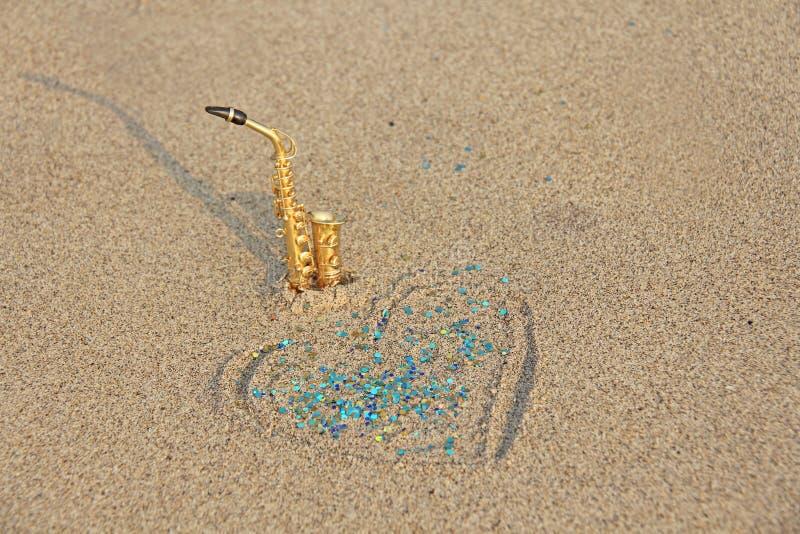 Złoci altowi saksofonów stojaki na piasku obok serca piasek i błękitny jaśnienie Romantyczny muzykalny tło musical obraz royalty free