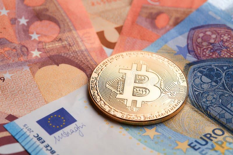 Złoci bitcoins brogujący na euro banknotu tle obraz stock