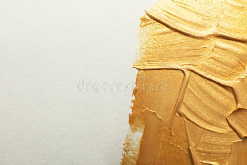 Złoci farby muśnięcia uderzenia na białym tle fotografia stock