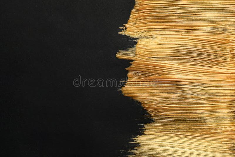 Złoci farby muśnięcia uderzenia na czarnym tle zdjęcia royalty free