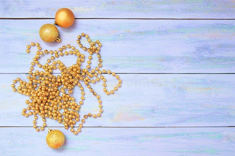 Złoci koraliki smyczkowe i Bożenarodzeniowe piłki Na błękitnym drewnianym tle fotografia stock