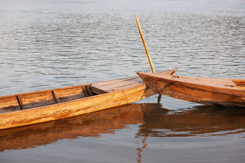 Złoci lekcy połysk zestrzelają wokoło dwa starą drewnianą łódź w wieczór Tradycyjna Tajlandzka łódź rybacka pod zmierzchem odbija zdjęcia royalty free