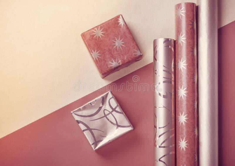 Złoci prezentów pudełka i czerwony opakunkowy papier na jaskrawym tle obraz royalty free