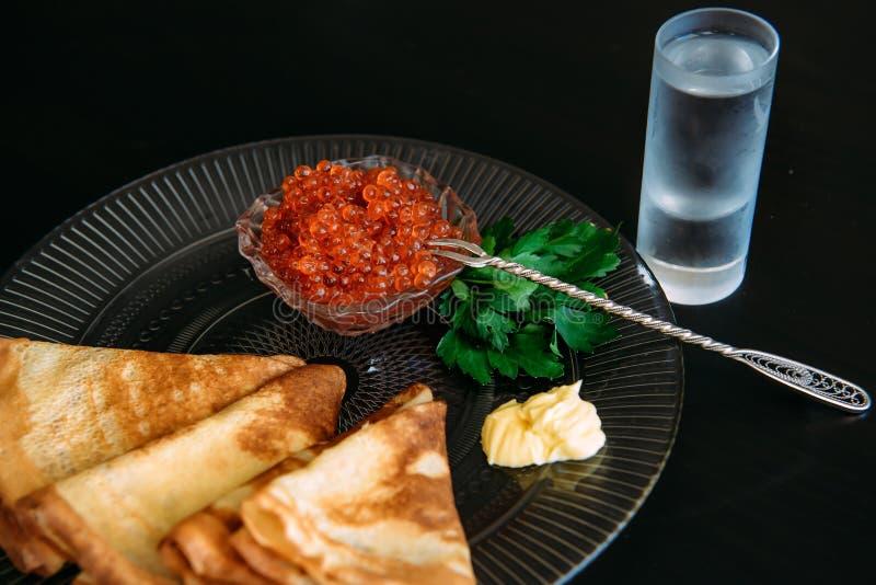 Złoci rosyjscy bliny z czerwonym kawiorem i masłem w przejrzystym talerzu blisko szkła odizolowywającego na czarnym tle lodowa aj fotografia stock