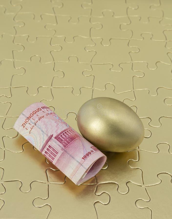 Złocista łamigłówka z Chińskim pieniądze i gniazdowym jajkiem obrazy stock