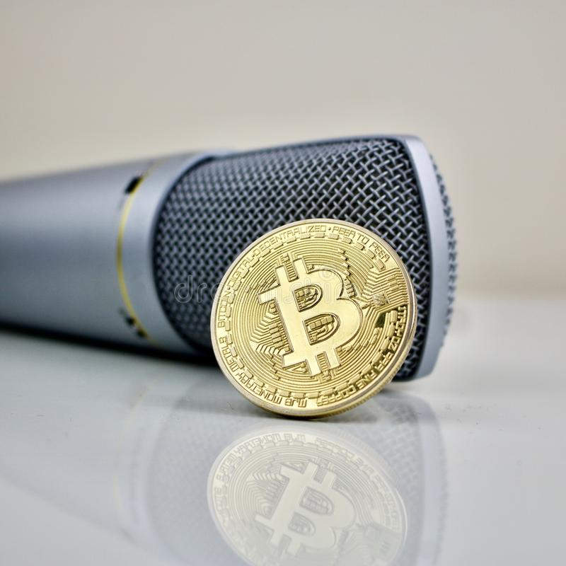 Złocista bitcoin moneta, mikrofon i fotografia stock