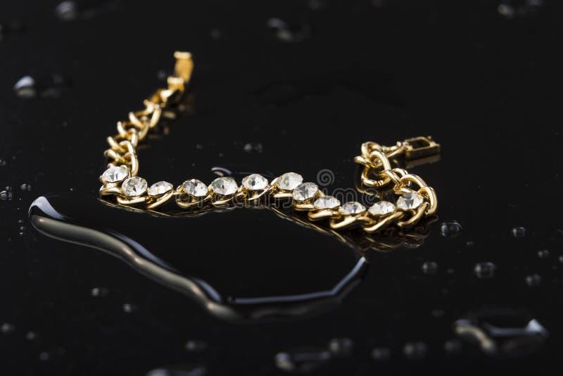 Złocista bransoletka z kamieniami na czarnym plastikowym tle obrazy royalty free