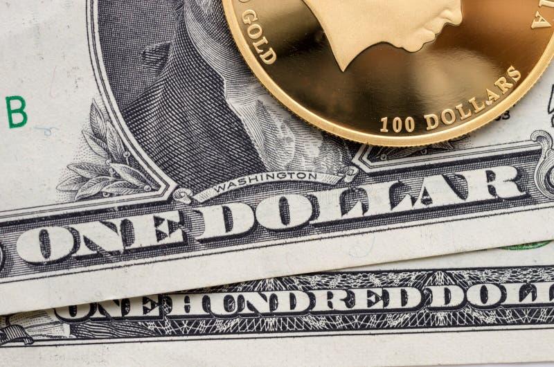 Złocista moneta z wartością nominalną 100 dolarów i dolarowych rachunki zdjęcia royalty free
