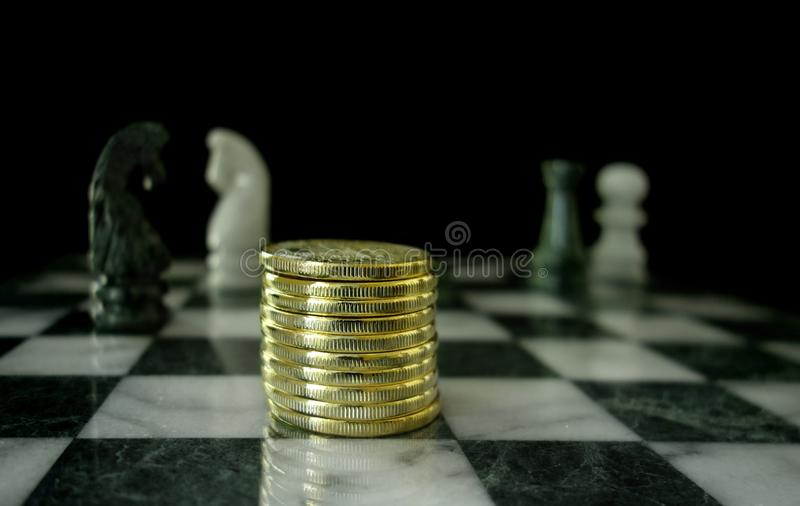 Złociste monety na szachowej desce obraz royalty free