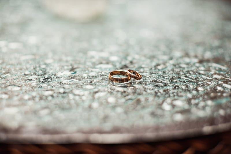 Złociste obrączki ślubne między kroplami obraz royalty free