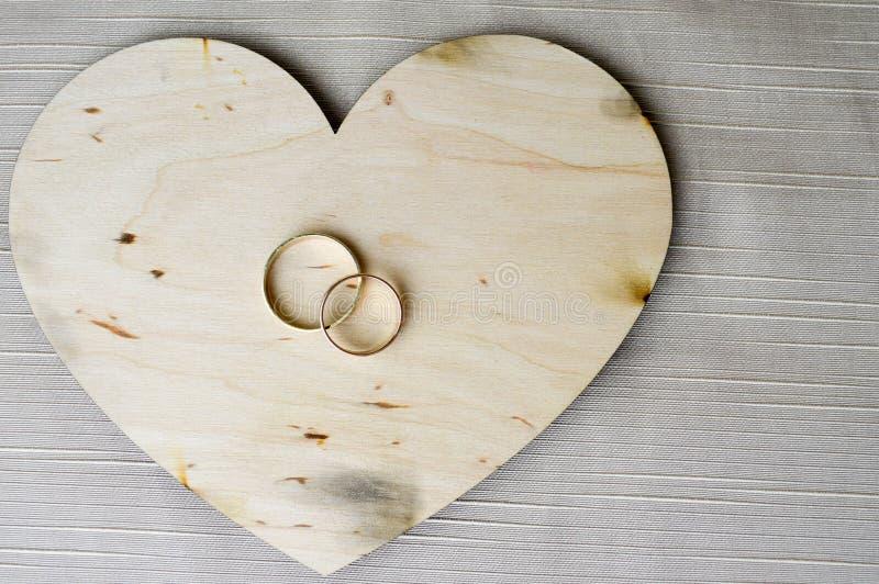 Złociste obrączki ślubne na drewnianym sercu Jaskrawy, połyskujący, wspaniali, modni, drodzy serca robić drewno z przybraniami fo obrazy stock